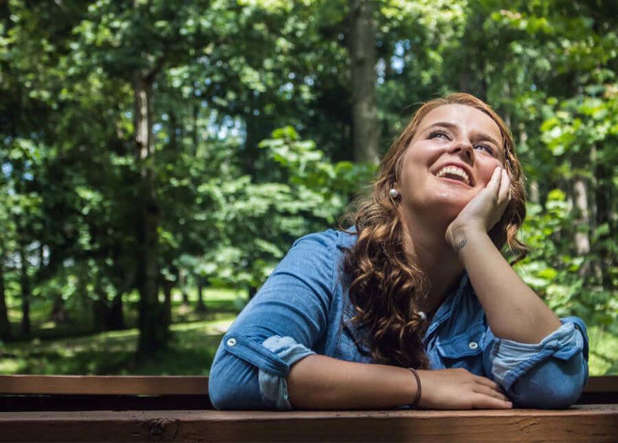 Vrouw spijkerjasje lachend bos